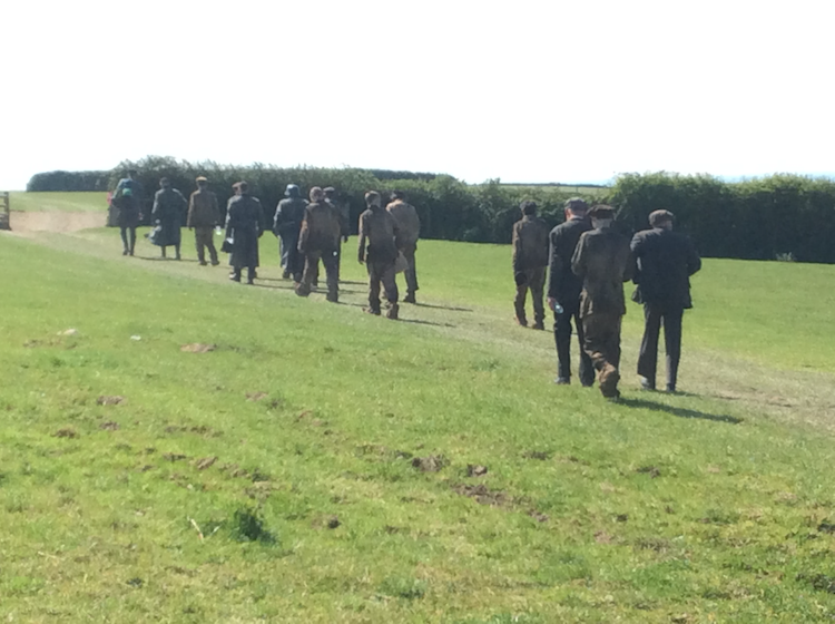 Some of the cast dressed as German Prisoners of War walking through one of our fields